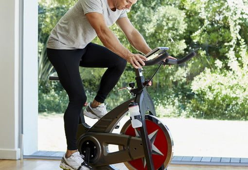 man working out on exercise bike at home 510x510 c ar1